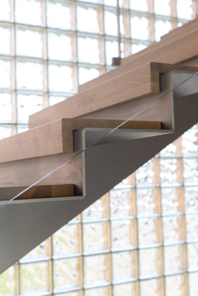 Dettaglio gradini- scala a giorno in metallo e legno con parapetto in vetro