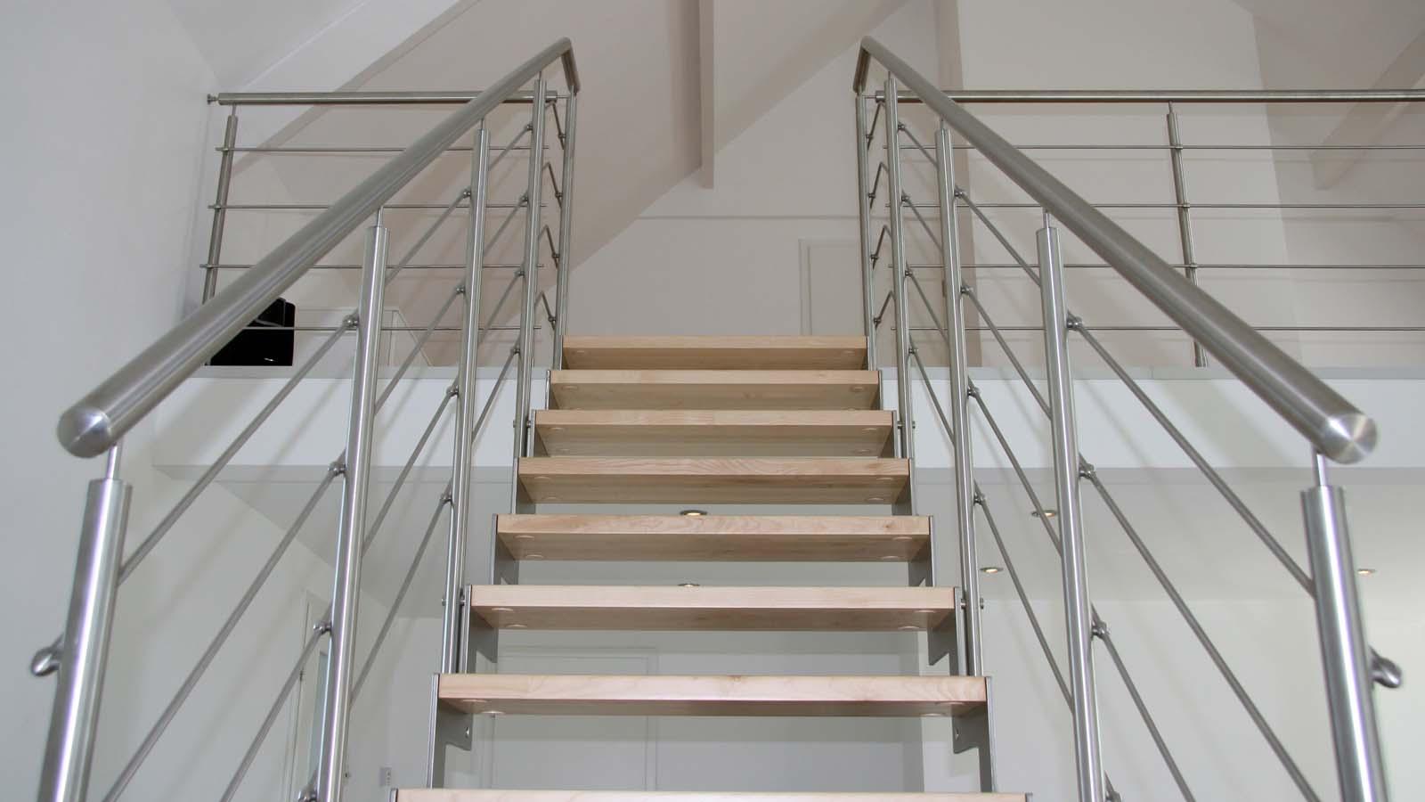 Dettaglio gradini a vista in legno con balaustra in acciaio