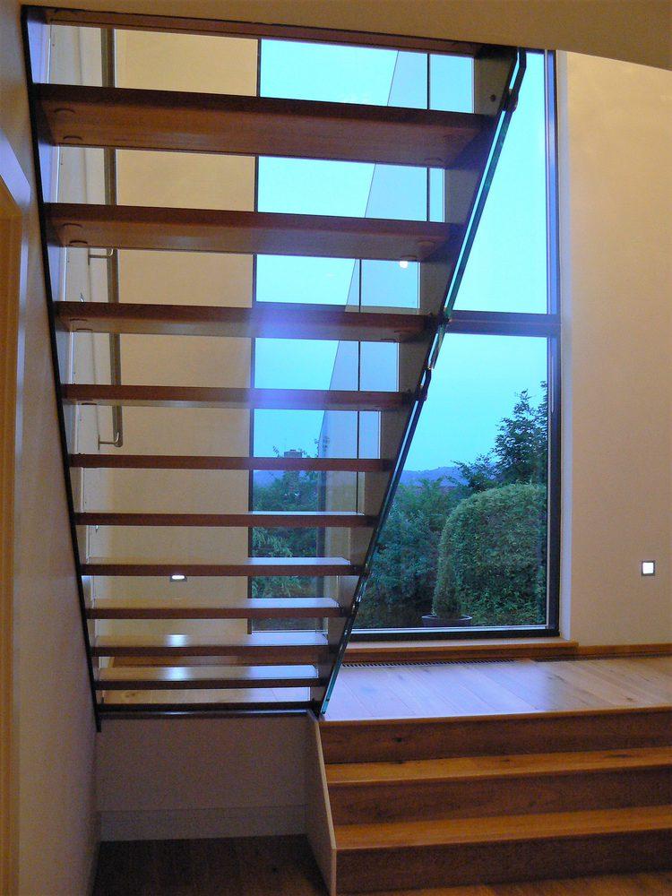 Dettaglio scalinata a giorno in legno, metallo e vetro