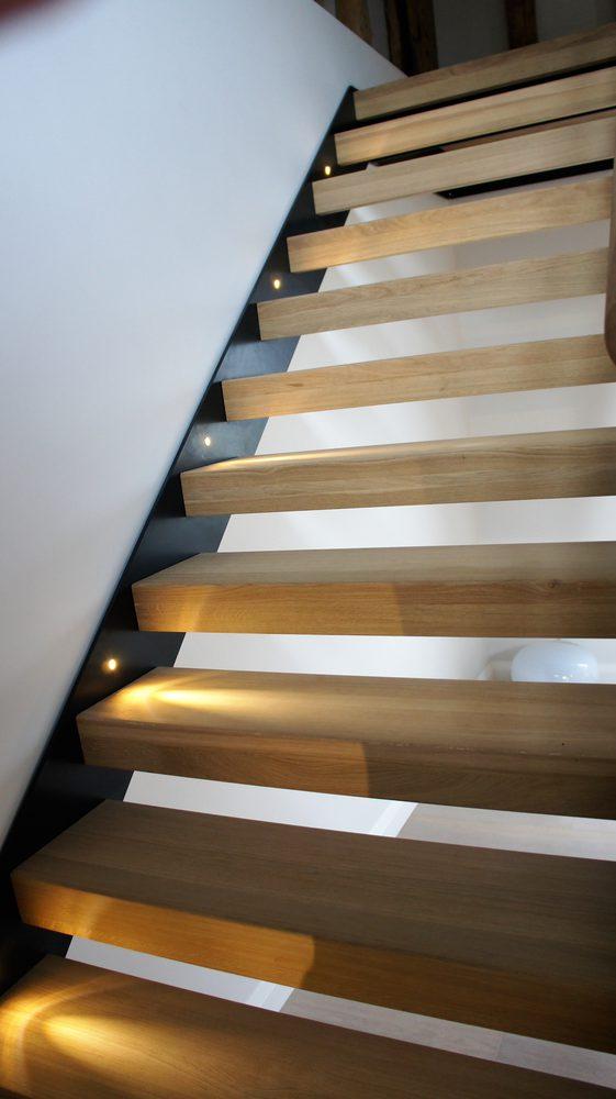 Dettaglio gradini e balaustra in vetro per scala di design da interni in legno
