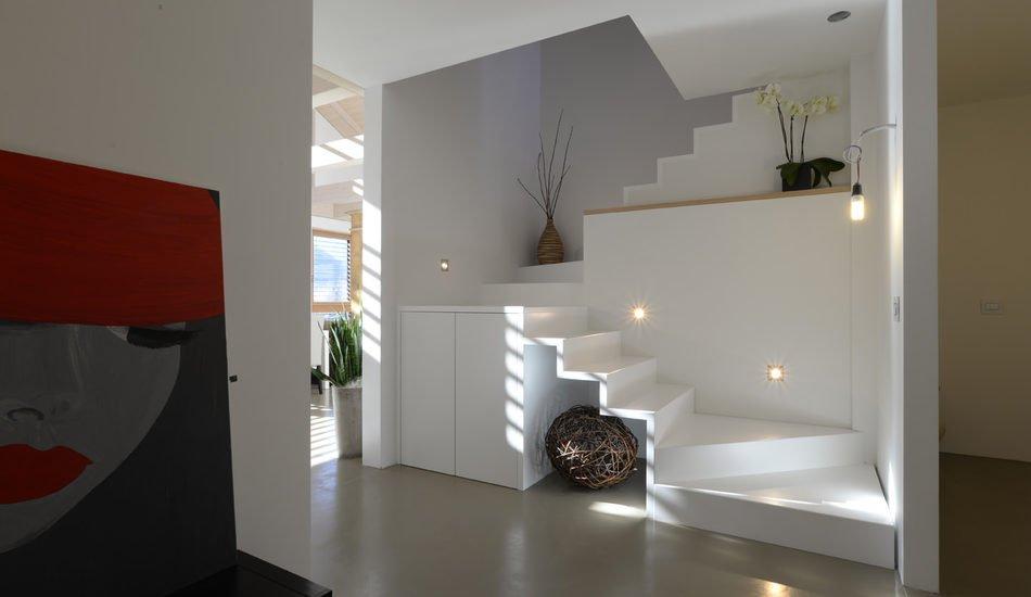 scala-arredo di design in legno in legno massello laccato bianco con verniciatura all'acqua, esaltato dal moderno pavimento in resina grigia.