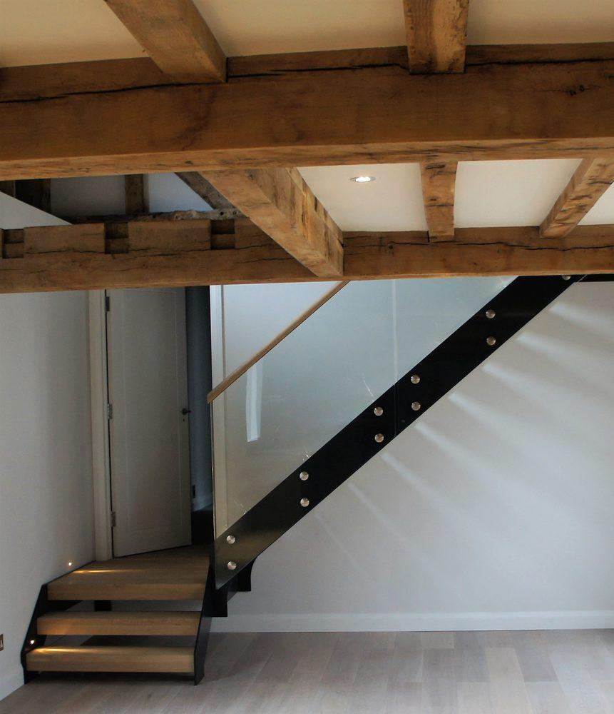 Travi a vista con scala in legno chiaro e metallo