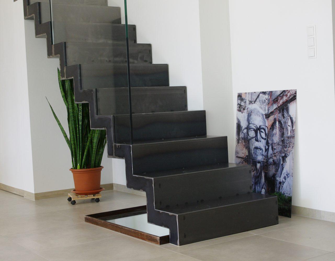 Dettaglio gradino scala a giorno per interni in metallo nero con parapetto in vetro