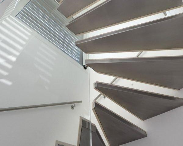 scala con gradini scatolati in acciaio inox e corrimano in acciaio e ringhiera in vetro