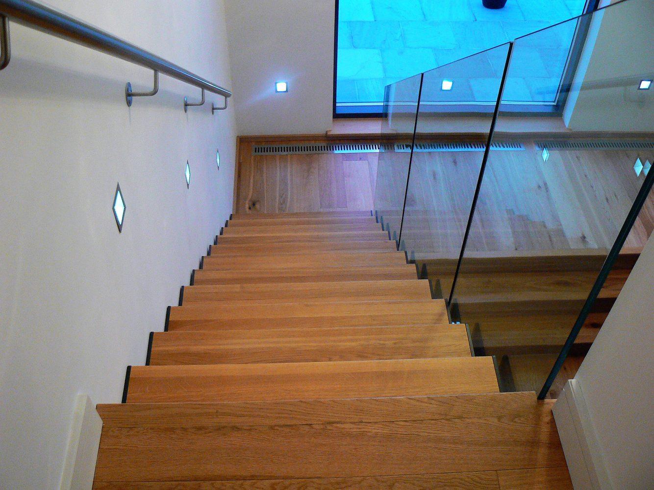 Dettaglio gradini in legno- scalinata a giorno in legno, metallo e vetro