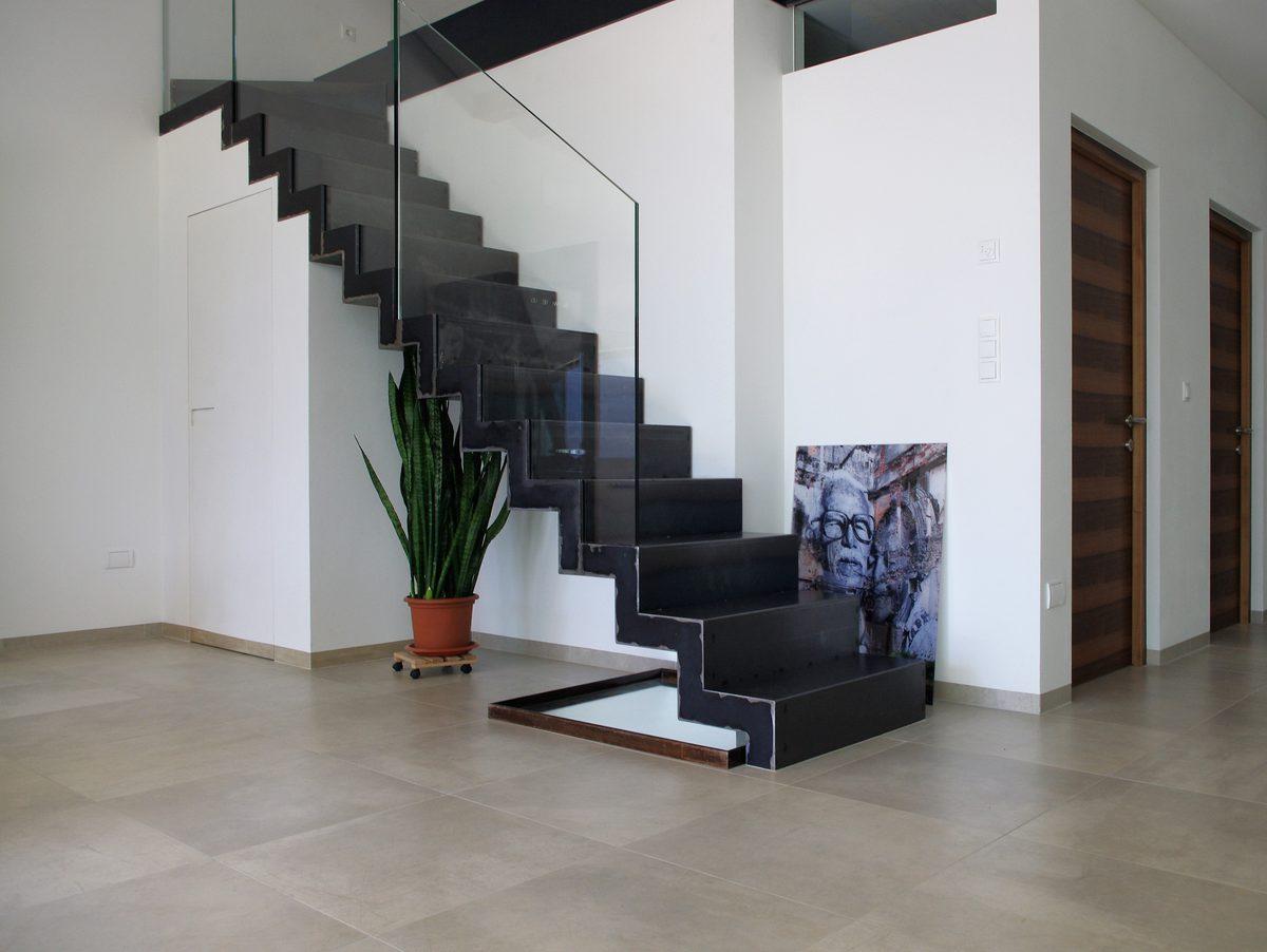Vista scala a giorno per interni in metallo nero con parapetto in vetro