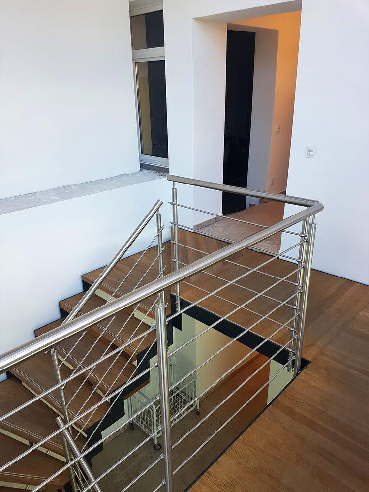 Dettaglio ringhiera aperta in metallo per scala da interni in legno