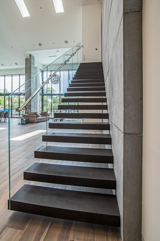 Particolare Scala a giorno in metallo con gradini a sbalzo e parapetto in vetro per ufficio