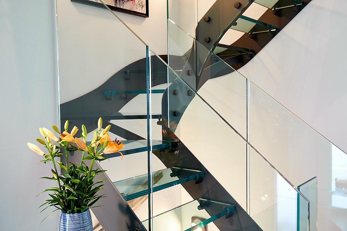 Dettaglio-Scala di design in vetro e metallo con balaustra in vetro
