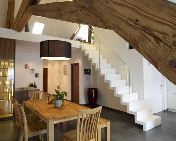 Scala realizzata in legno lamellare di faggio laccato bianco con parapetti in vetro, alloggiati nella struttura.
