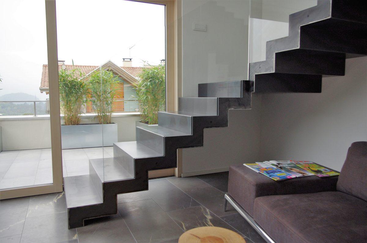 Scala di design a giorno in metallo nera con parapetto in vetro