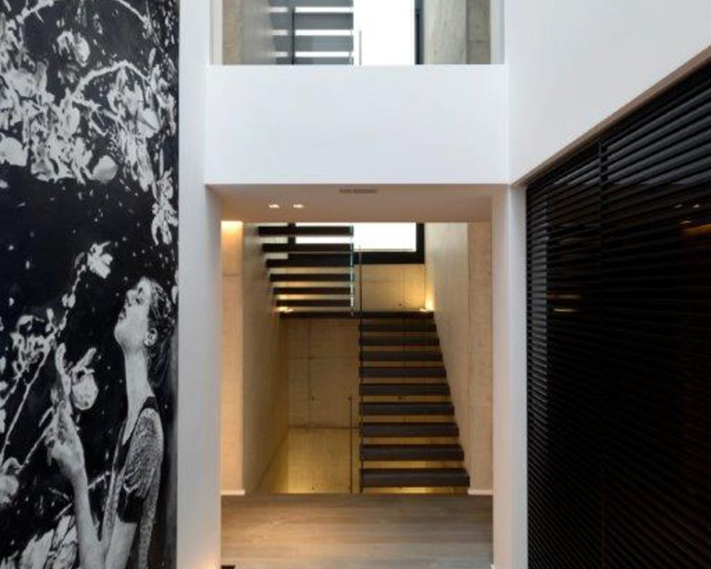 Scala a sbalzo di alto design con gradini in ferro saldamente inseriti in un fascione a muro e ringhiera in vetro