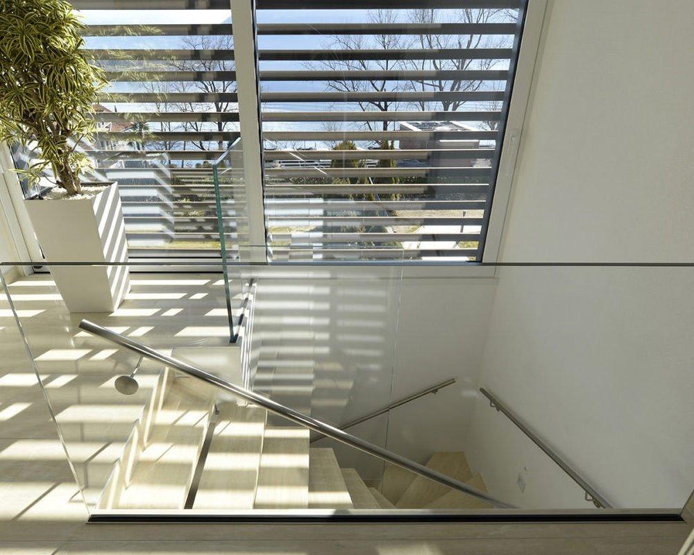 scala con gradini scatolati in acciaio inox e corrimano ijn acciaio e ringhiera in vetro