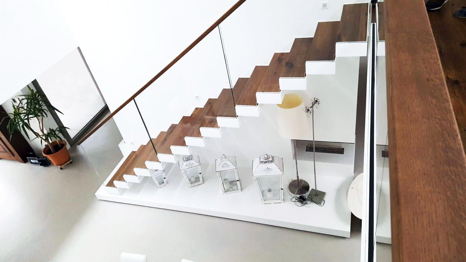 scala in ferro a sbalzo su misura con balaustra in vetro di qualità extrachiara, corredata di corrimano in legno di noce