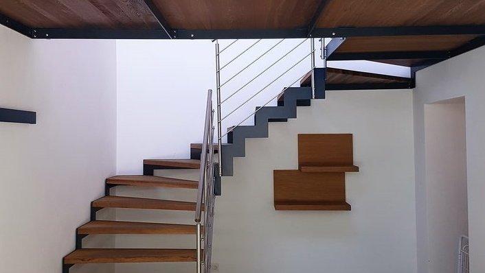 Scala a giorno in legno e metallo con contrasti neri e ringhiera in metallo aperta