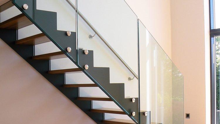 Dettaglio parapetto in vetro per scala a giorno in legno, metallo e vetro